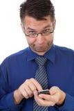 Mannelijke nerdy geek begrijpt niets van zijn telefoon Royalty-vrije Stock Fotografie