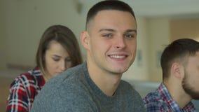 Mannelijke niet-gegradueerdenglimlachen bij de lezingszaal royalty-vrije stock afbeelding