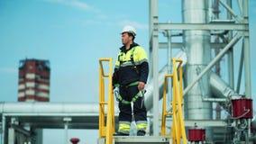 Mannelijke olie of gasfabrieksarbeider die naar de toren van het observatiedek voor controle bedrijfsveiligheid gaan stock videobeelden