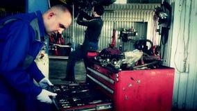 Mannelijke onderhoudsingenieur die hulpmiddelen in lade schikken op autoworkshop stock footage