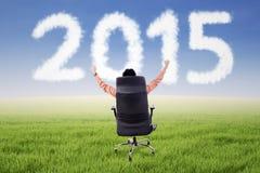 Mannelijke ondernemer op stoel met nummer 2015 Stock Fotografie