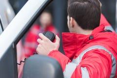 mannelijke paramedicus die door draagbare radio spreken en iets tonen stock afbeeldingen
