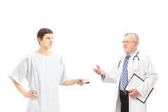Mannelijke patiënt in het ziekenhuistoga die steekpenning aanbieden aan een medische arts Stock Foto's