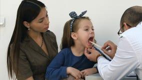 Mannelijke pediater die keel van meisjezitting onderzoeken met haar mamma royalty-vrije stock afbeeldingen