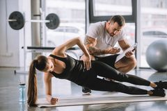 Mannelijke persoonlijke trainer die tijdopnemer en jonge atletische vrouw bekijken royalty-vrije stock afbeelding