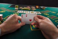 Mannelijke pookspeler die de hoeken van twee kaartenazen opheffen Royalty-vrije Stock Foto