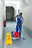 Mannelijke Portier Cleaning Floor stock afbeeldingen