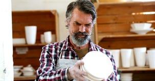 Mannelijke pottenbakker die ceramische boog 4k controleren stock footage