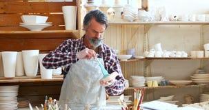 Mannelijke pottenbakker die het ceramische kunstwerk 4k schilderen stock footage