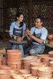 Mannelijke pottenbakker die vrouwelijke pottenbakker bijstaan Stock Foto's