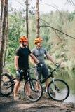 mannelijke proeffietsers in helmen met bergcycli die met sportflessen water dichtbij rivier rusten stock foto's