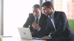 Mannelijke professionele beleggingsadviseur raadplegende cli?nt met laptop op vergadering stock videobeelden