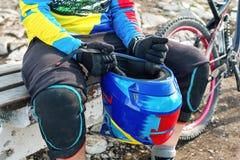 Mannelijke raceauto mtb fietser in beschermende uitrusting die klaar voor ras die volledige gezichtshelm houden worden stock foto