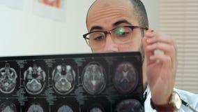 Mannelijke radioloog die hersenen gegevens verwerkte tomografie onderzoeken stock footage