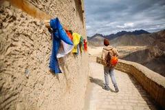 Mannelijke reiziger die in het klooster met kleurrijke gebedvlaggen lopen in Leh, Ladakh, India stock fotografie