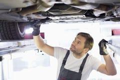 Mannelijke reparatiearbeider die auto in workshop onderzoeken Stock Afbeeldingen