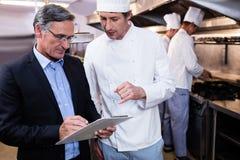 Mannelijke restaurantmanager die op klembord schrijven terwijl het op elkaar inwerken aan hoofdchef-kok stock foto