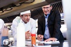 Mannelijke restaurantmanager die op klembord schrijven terwijl het op elkaar inwerken aan hoofdchef-kok stock fotografie