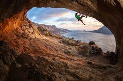 Mannelijke rotsklimmer die langs een dak in een hol beklimmen stock foto