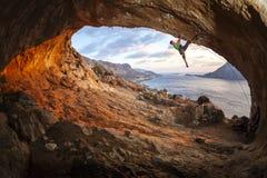Mannelijke rotsklimmer die langs een dak in een hol beklimmen stock foto's