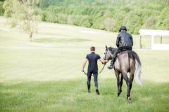 Mannelijke ruiters die met paard op de groene weide lopen Stock Foto's