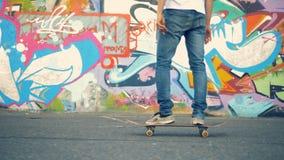 Mannelijke ruitertribunes omhoog op zich een skateboard en begin het bewegen stock video