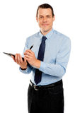 Mannelijke secretaresse die onderaan nota's van werkgever neemt Royalty-vrije Stock Foto's