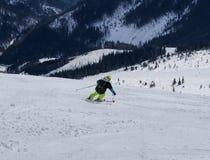 Mannelijke skiër die bergaf ski?en Jongen die neer op skis dalen Snijd positie Atleticcijfer Gele helm Zwarte rugzak gevaarlijk royalty-vrije stock afbeeldingen