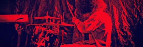 Mannelijke slagwerker met Afro-uitrusting van de haar de speeltrommel in nachtclub royalty-vrije stock foto