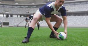 Mannelijke speler die rugbybal in de grond overgaan bij stadion 4k stock footage