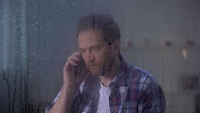 Mannelijke sprekende telefoon op middelbare leeftijd met familie achter regenachtige dag, ontbrekende verwanten stock videobeelden