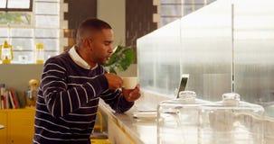 Mannelijke stafmedewerker die koffie hebben terwijl het gebruiken van laptop in cafetaria 4k stock footage