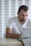 mannelijke student die aan zijn laptop werkt Stock Foto