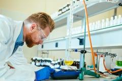 Mannelijke student die chemie in laboratorium werken royalty-vrije stock afbeeldingen