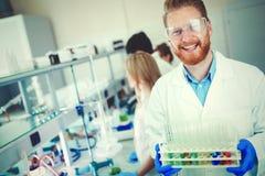 Mannelijke student die chemie in laboratorium werken stock afbeelding