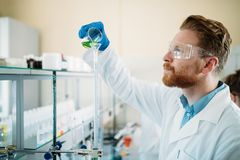 Mannelijke student die chemie in laboratorium werken stock fotografie