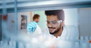 Mannelijke student die chemie in laboratorium werken stock foto