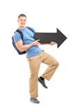Mannelijke student die een grote zwarte pijl houden Royalty-vrije Stock Afbeelding