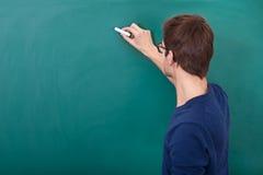 Mannelijke student die op bord schrijven stock afbeeldingen
