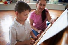 Mannelijke Student Enjoying Piano Lesson met Leraar stock afbeelding