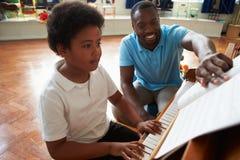 Mannelijke Student Enjoying Piano Lesson met Leraar stock foto's