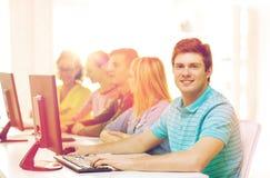 Mannelijke student met klasgenoten in computerklasse stock fotografie