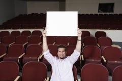 Mannelijke Student Raising Sign Board terwijl het Zitten in Klaslokaal royalty-vrije stock fotografie