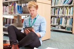Mannelijke Student Studying In Library met Digitale Tablet Stock Fotografie
