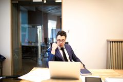 Mannelijke succesvolle ondernemer die aan een arbeidsovereenkomst op netbook werken stock foto's