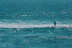 Mannelijke surfer die op de grootste golf in de oceaan wachten stock afbeelding