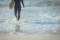 Mannelijke surfer met een surfplank die op een strand lopen royalty-vrije stock foto