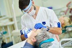 Mannelijke tandarts aan het werk in kliniek stock fotografie