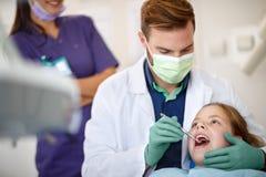 Mannelijke tandarts die kind` s tanden met tandspiegel onderzoeken stock fotografie