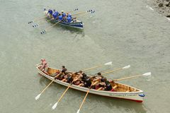 Mannelijke teams bij het roeien van boten in Clovelly, Devon Stock Foto's